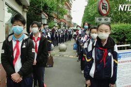 Школярі в Пекіні та Шанхаї попри епідемію повертаються за парти