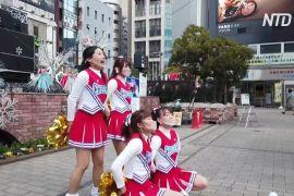 Чирлідери танцюють біля вокзалу в Токіо, щоб підбадьорити людей