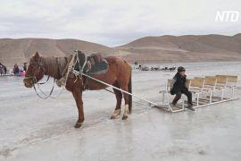 Киргизькі туристи катаються по високогірному озері на саморобних санках